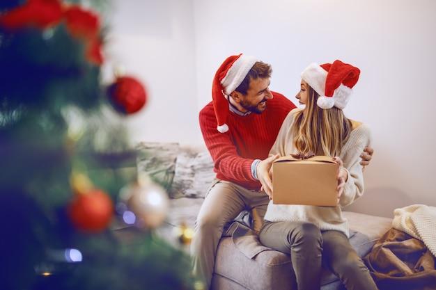 Donna bionda caucasica sveglia stupita che si siede sul sofà in salone e che riceve regalo dal suo ragazzo. entrambi hanno cappelli di babbo natale in testa. in primo piano è l'albero di natale. interno soggiorno.