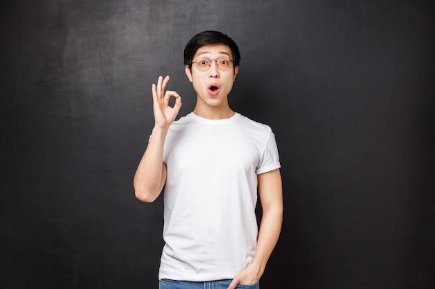 Stupito ed entusiasta giovane ragazzo asiatico sorpreso lasciato senza parole e colpito dopo aver visto il premier del nuovo film, mostra il segno ok sembra stupito in piedi