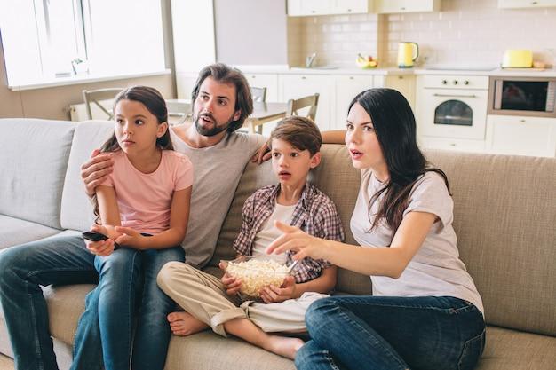 La famiglia stupita si siede sul divano e guarda la tv