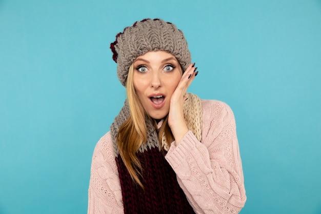 Femmina stupita nel cappello e sciarpa e maglione invernali.