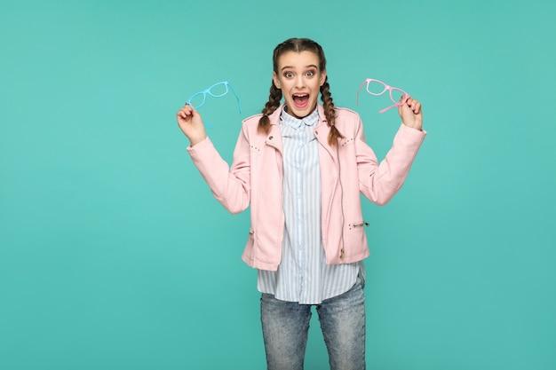 Ragazza stupita in stile casual o hipster, acconciatura a codino, in piedi, con in mano occhiali blu e rosa e guardando la telecamera con faccia sorpresa, ripresa in studio al coperto, isolata su sfondo blu o verde