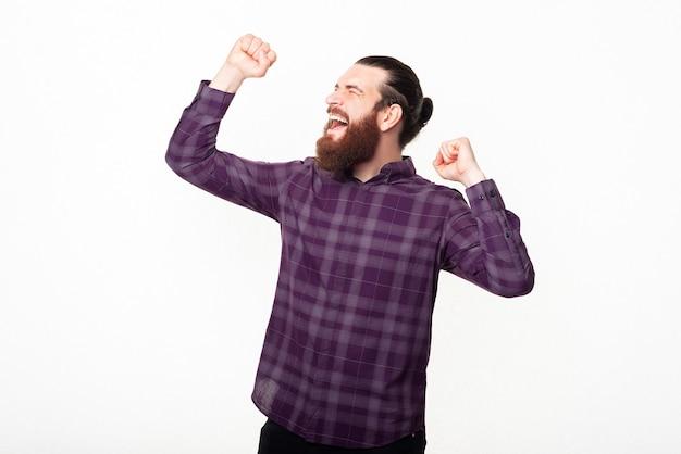 Uomo barbuto bello stupito che celebra con i pugni in su
