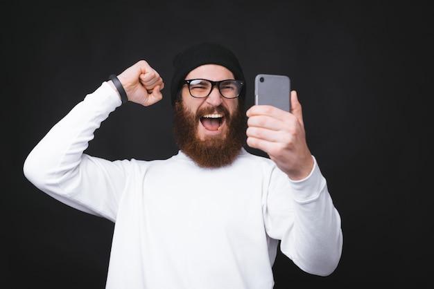 Uomo bello stupito che celebra e che esamina smartphone