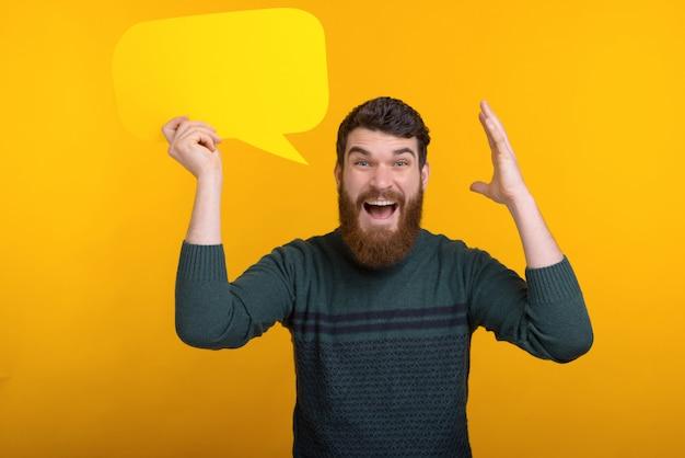 Uomo bello stupito con la barba che tiene fumetto giallo