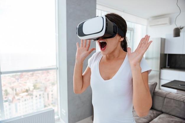Giovane donna felice e stupita con le mani alzate e la bocca aperta usando i google della realtà virtuale a casa