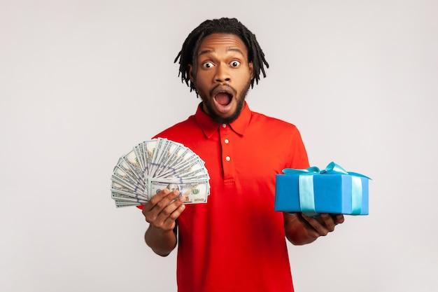 Uomo stupito che tiene in mano molti soldi e presenta una scatola, scioccato dai bonus, omaggio.