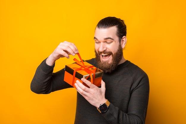 Uomo stupito con la barba che apre confezione regalo su giallo