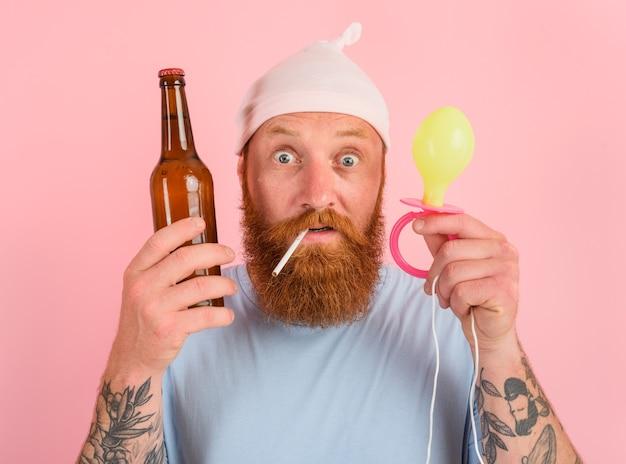 L'uomo stupito con barba e tatuaggi si comporta come un piccolo neonato con la birra in mano