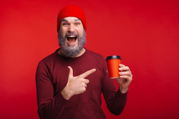 Uomo stupito con la barba bianca che punta alla tazza di caffè rossa