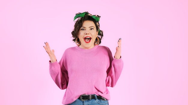 Donna alla moda stupita scioccata dicendo wow. giovane femmina sorpresa sopra la parete rosa. persona emotiva.