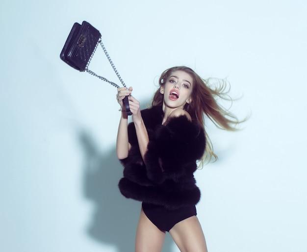 La donna stupita o la ragazza sexy carina in gilet o panciotto di pelliccia nera tiene la borsa alla moda con catena su bianco