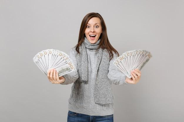 Donna stupita in sciarpa maglione grigio che tiene la bocca aperta, con in mano un sacco di banconote in dollari, denaro contante isolato su sfondo grigio. stile di vita sano, emozioni delle persone, concetto di stagione fredda.