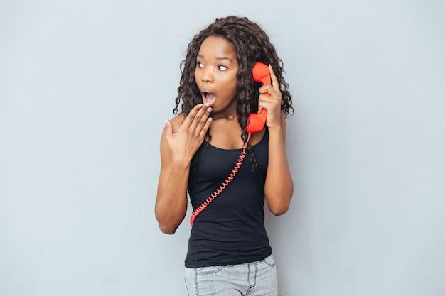 Donna stupita che parla sul tubo del telefono retrò e distoglie lo sguardo sul muro grigio
