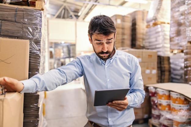 Supervisore barbuto attraente giovane stupito in piedi in magazzino e guardando tablet