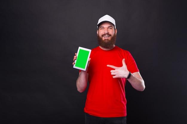 Uomo giovane barbuto hipster stupito in maglietta rossa che punta allo schermo verde sul tablet