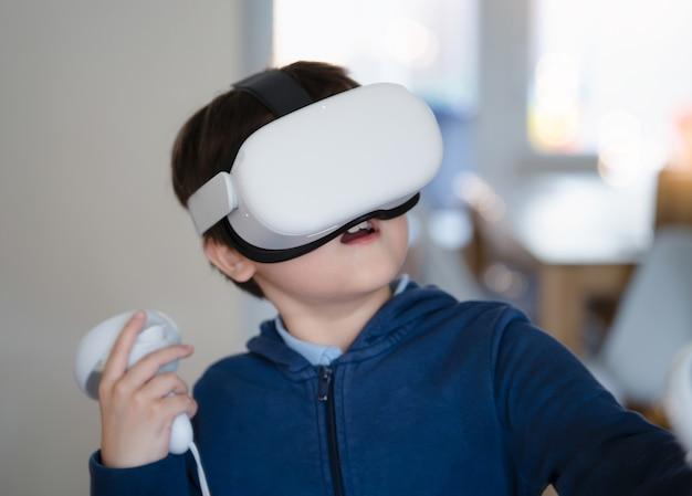 Ragazzino stupito che indossa occhiali per realtà virtuale. ragazzo emotivo che gioca ai videogiochi guardando in cuffia vr. ritratto di ragazzo di razza mista che sperimenta gadget 3d in soggiorno.