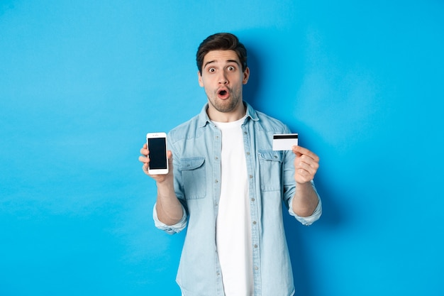 Giovane stupito che mostra lo schermo del cellulare e la carta di credito, acquista online, in piedi su sfondo blu