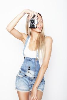 Giovane donna graziosa stupita che tiene la macchina fotografica su sfondo bianco.