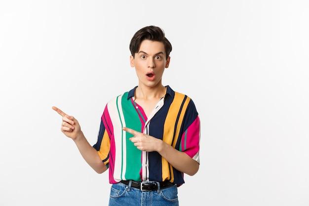 Stupito giovane uomo queer che punta il dito a sinistra, fissando la telecamera con incredulità, facendo domande sul prodotto, in piedi su sfondo bianco.