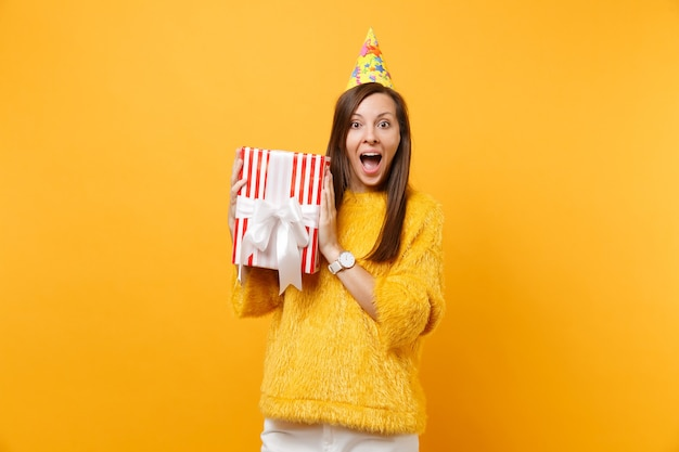 La giovane donna stupita in cappello della festa di compleanno tiene la scatola rossa con il regalo presente che celebra godendo la festa isolata su fondo giallo luminoso. persone sincere emozioni, concetto di stile di vita. zona pubblicità.