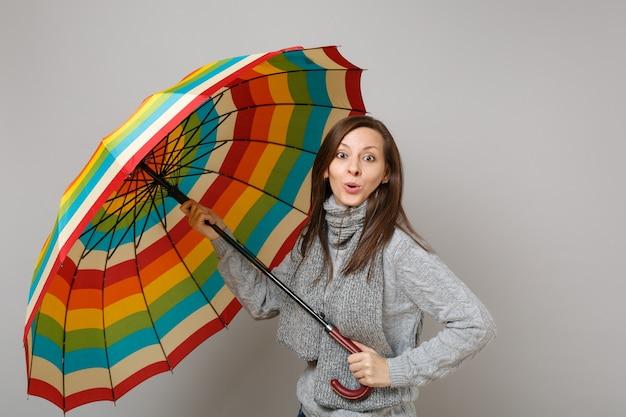 Giovane donna stupita in maglione grigio, sciarpa che tiene ombrello colorato isolato su sfondo grigio in studio. stile di vita sano, persone sincere emozioni, concetto di stagione fredda. mock up copia spazio.