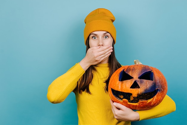 Giovane donna stupita che tiene la bocca della copertura della grande zucca intagliata spettrale con la mano