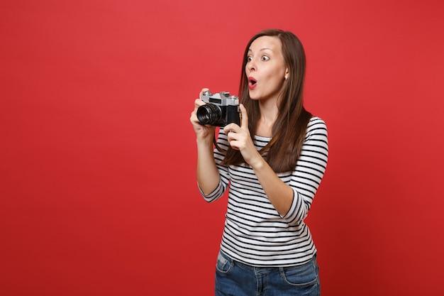 Giovane donna stupita che tiene la macchina fotografica d'epoca retrò tenendo la bocca spalancata, guardando sorpreso isolato su sfondo rosso brillante della parete. persone sincere emozioni, concetto di stile di vita. mock up copia spazio.