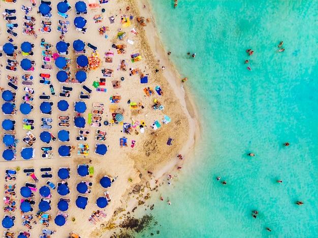 Incredibile vista aerea dall'alto sulla spiaggia di nissi a cipro. spiaggia di nissi con l'alta marea. i turisti si rilassano sulla spiaggia. spiaggia affollata con molti turisti. un luogo popolare.