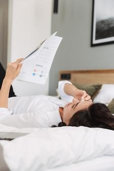Incredibile bella giovane donna d'affari in abiti da cerimonia al chiuso a casa si trova sul letto parlando al telefono con documenti cartacei.