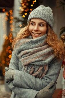Incredibile bella giovane donna felice con un sorriso magico in vestiti a maglia in un cappello grigio lavorato a maglia con un'elegante sciarpa calda sulla strada vicino alle luci in vacanza