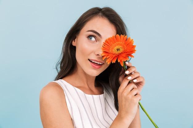 Fiore della holding della parete isolata bella giovane donna stupefacente.