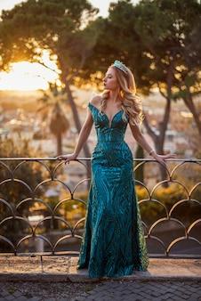 Corona da portare della donna bionda stupefacente al tramonto