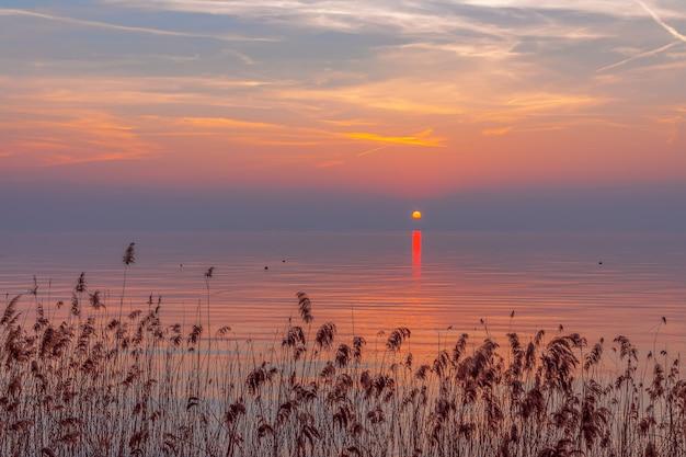 Incredibile tramonto colorato con nebbia sul lago di garda, italia