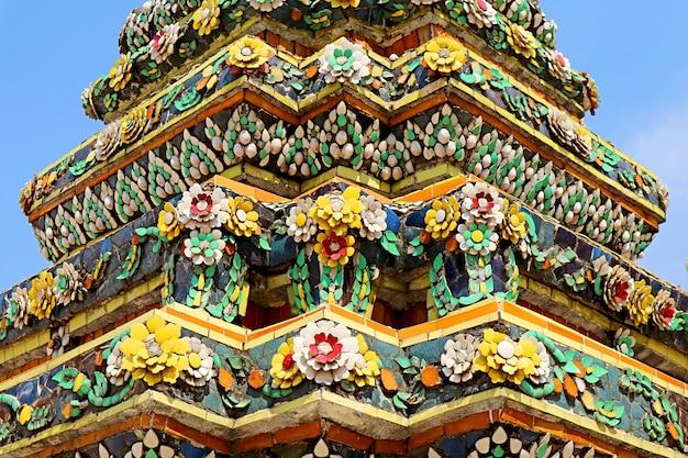 Incredibili dettagli di piastrelle di ceramica colorate e conchiglie dello stupa chiama phra maha chedi si rajakarn nel complesso del tempio di wat pho, bangkok, thailandia