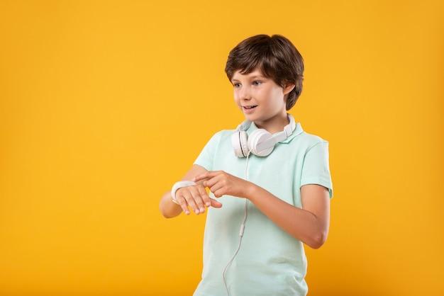 Dispositivo straordinario. felice ragazzo dai capelli scuri che pensa e guarda l'orologio