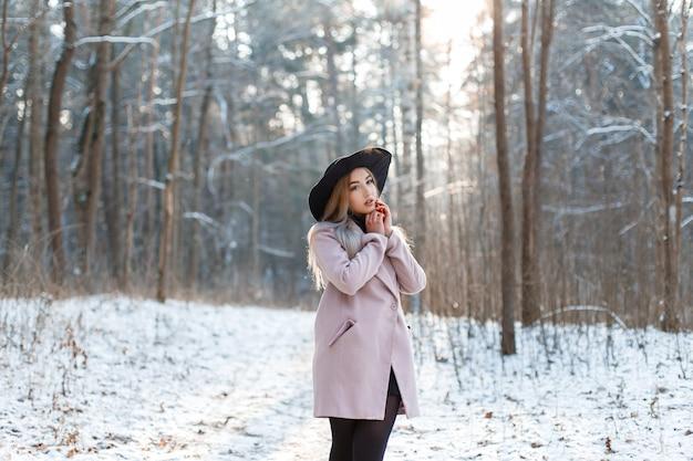 Incredibile giovane donna alla moda in un elegante cappotto rosa in un lussuoso cappello in un vestito elegante nero in posa in un parco invernale in una giornata di sole. ragazza fresca all'aperto