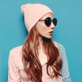 Incredibile ragazza vestito di moda autunno-primavera. tendenza hipster stile vaniglia cappello a cuffia swag girl. occhiali vintage alla moda. vibrazione rosa