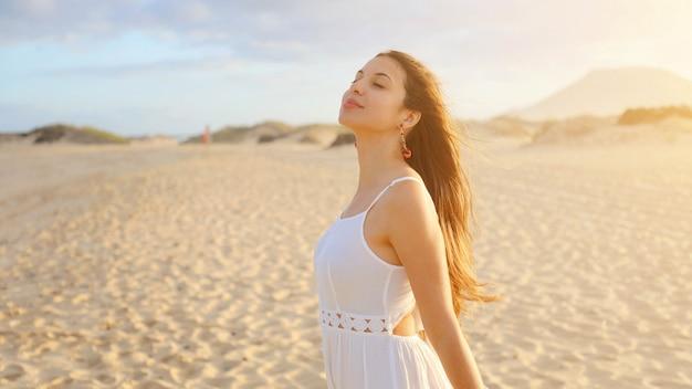 Incredibile ragazza nel deserto al tramonto. bella giovane donna di moda in abito bianco respirando godendo di relax sulla spiaggia.