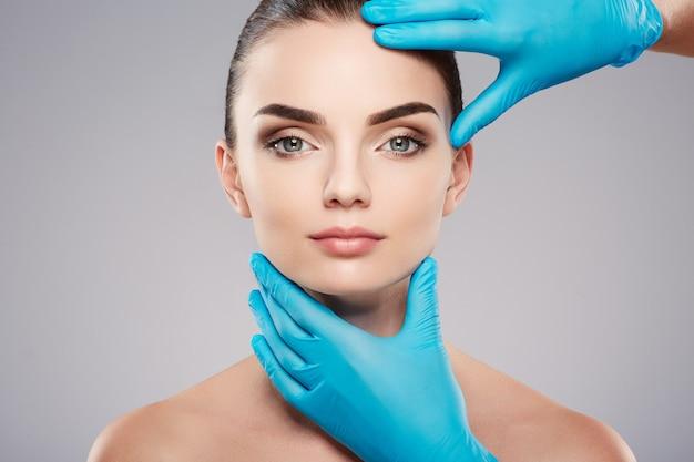 Incredibile ragazza con sopracciglia folte al fondo dello studio, mani del medico che indossano guanti blu vicino al viso del paziente, concetto di chirurgia, foto di bellezza.