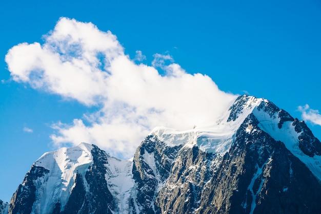 Incredibile ghiacciaio sotto il cielo blu. enorme nuvola su meravigliose montagne innevate al sole. atmosferico paesaggio montano minimalista di natura maestosa in una giornata di sole.