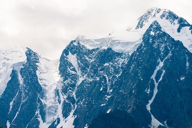 Incredibile enorme cima del ghiacciaio. catena montuosa innevata nel cielo coperto. meravigliosa cresta rocciosa gigante con neve nella nebbia. atmosferico paesaggio minimalista di maestosa natura degli altopiani. tranquillo paesaggio montano.