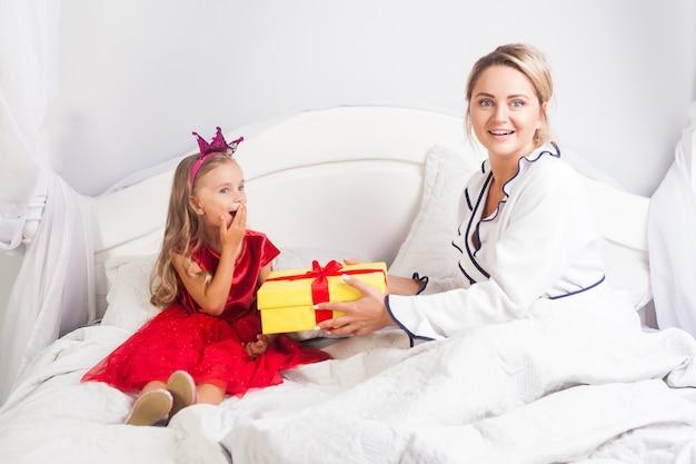 Incredibile bambina in abito seduta a letto, che sembra sorpresa dalla confezione regalo della madre, donna che guarda la telecamera con stupore, saluto bambino la mattina del compleanno, congratulazioni in camera da letto