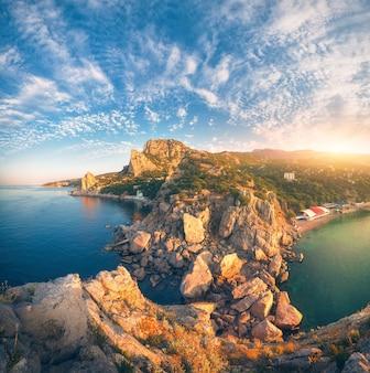Incredibile paesaggio di montagna all'alba. bella vista dalla vetta della montagna sul mare blu, rocce alte, spiaggia, foresta e cielo blu colorato con nuvole in estate. viaggio in europa. paesaggio marino