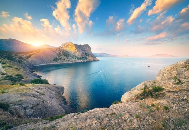 Incredibile paesaggio di montagna al tramonto. bella scena con montagne, mare blu, rocce alte, spiaggia, foresta e cielo blu colorato con nuvole in estate. viaggio in europa. paesaggio marino. sfondo della natura