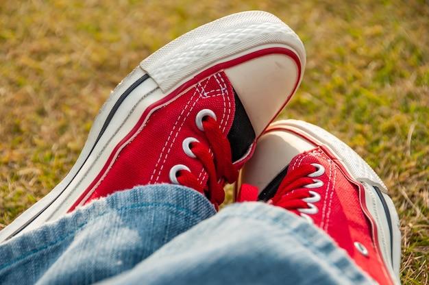 Incredibile paio di scarpe da ginnastica rosse che si guardano innamorate parzialmente coperte dai jeans