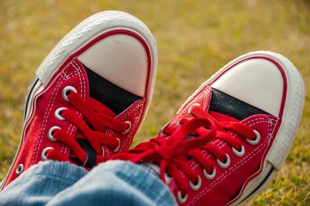 Incredibile paio di scarpe da ginnastica rosse che si guardano incontrarsi parzialmente coperte di jeans