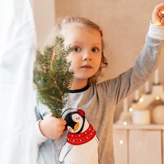 Incredibile ritratto di una bellissima bambina in pigiama alla moda con un ramo di un albero di natale e luci in una stanza luminosa. vacanze invernali