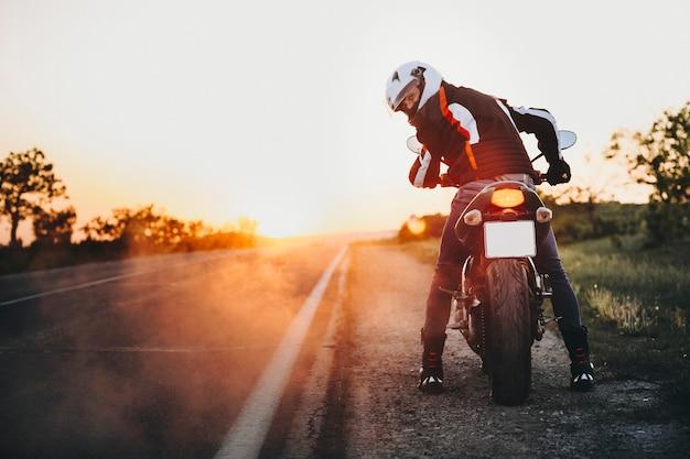 Incredibile ritratto di un motociclista caucasico seduto sulla sua bici pronto per andare ed esamina la macchina fotografica sopra la spalla contro il tramonto vicino alla strada mentre si viaggia in bicicletta.