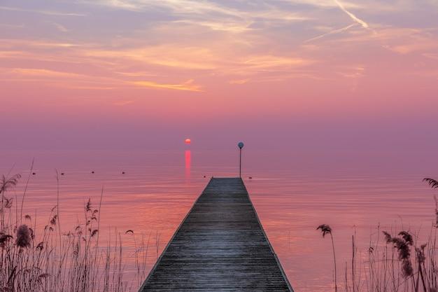 Incredibile tramonto viola con nebbia su un molo sul lago di garda, italia