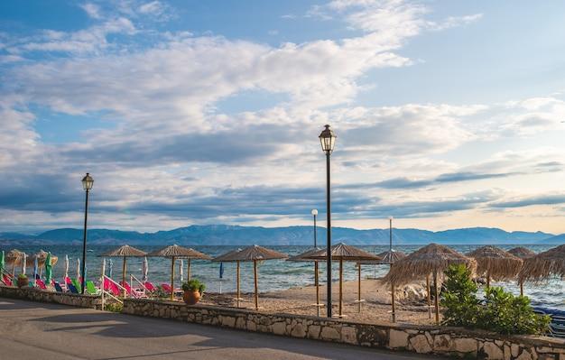 Incredibile strada vicino alla baia con acqua limpida sull'isola di corfù, in grecia. bellissimo paesaggio della spiaggia del mar ionio con sedie a sdraio colorate e ombrelloni.